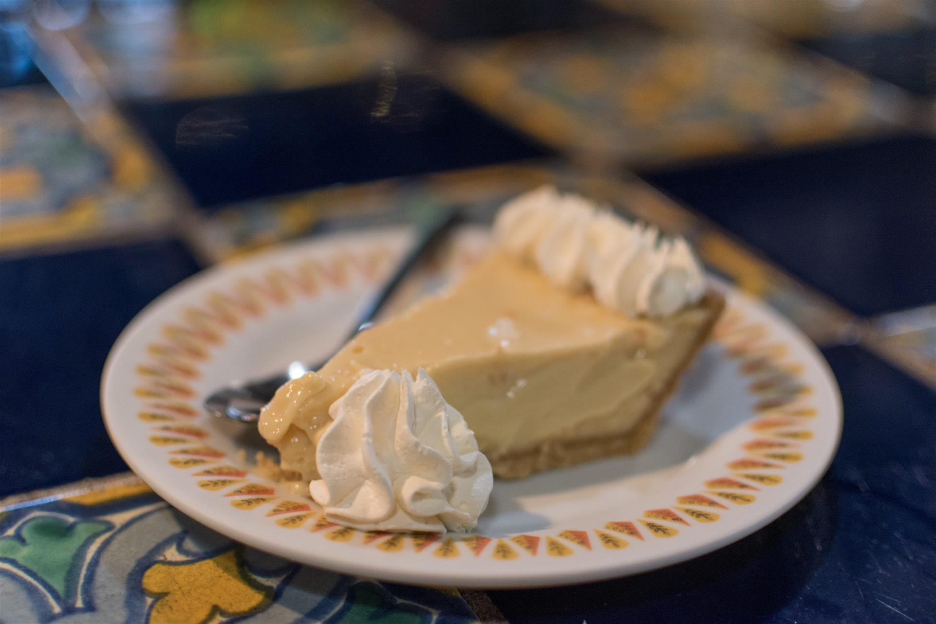 slice of key lime pie with a dallop of whipped cream and a spoon on a plate