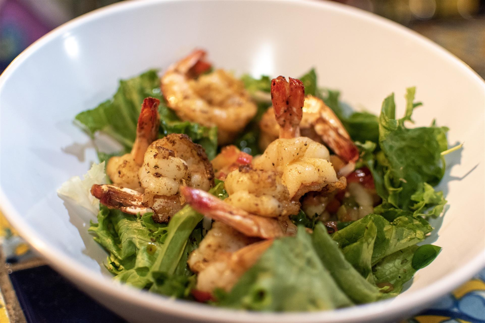 grilled shrimp over a bed of lettuce in a bowl