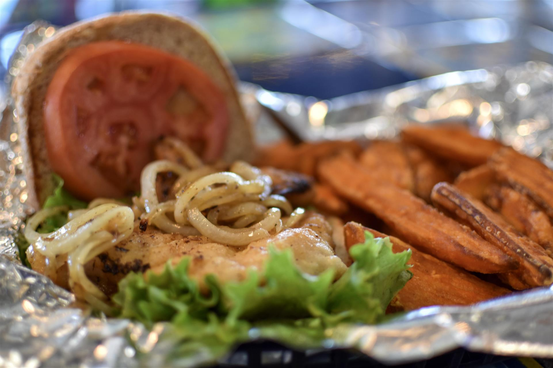open faced sandwich with tomato, lettuce, onions with a side of sweet potatoes