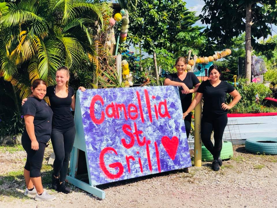 four employees standing along Camellia St Grill sign