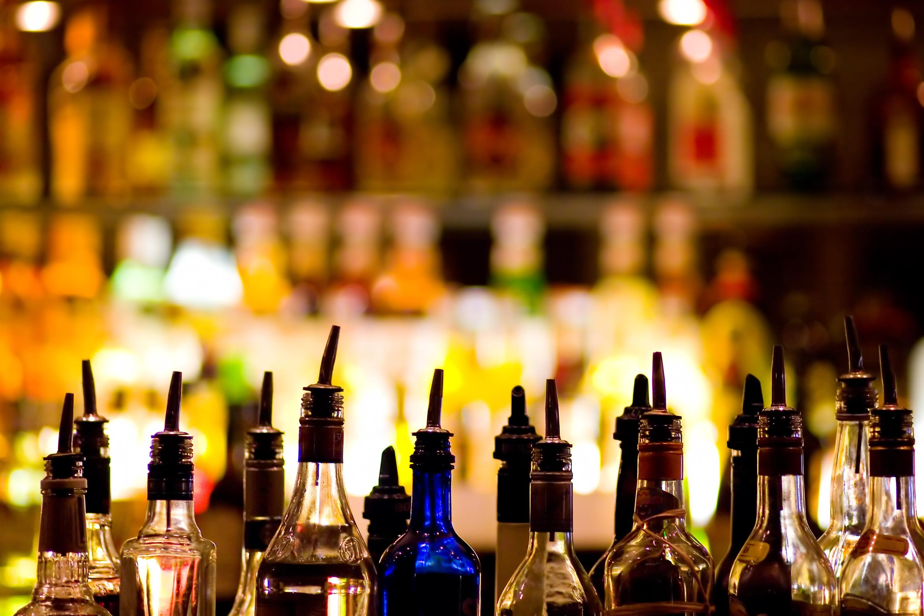 Bottles of liquor lined up in front of a bar