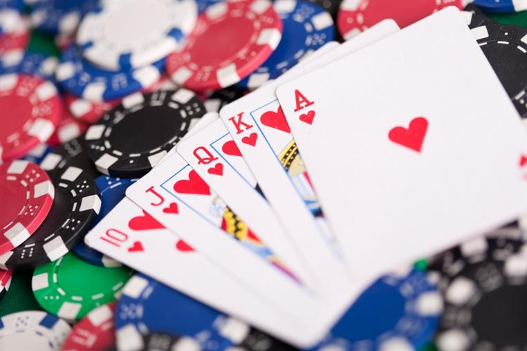 Playing cards fanned out across felt poker table surrounded by poker chips