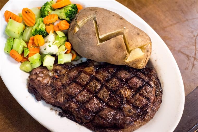 grilled steak with a baked potato and side of mixed vegetables