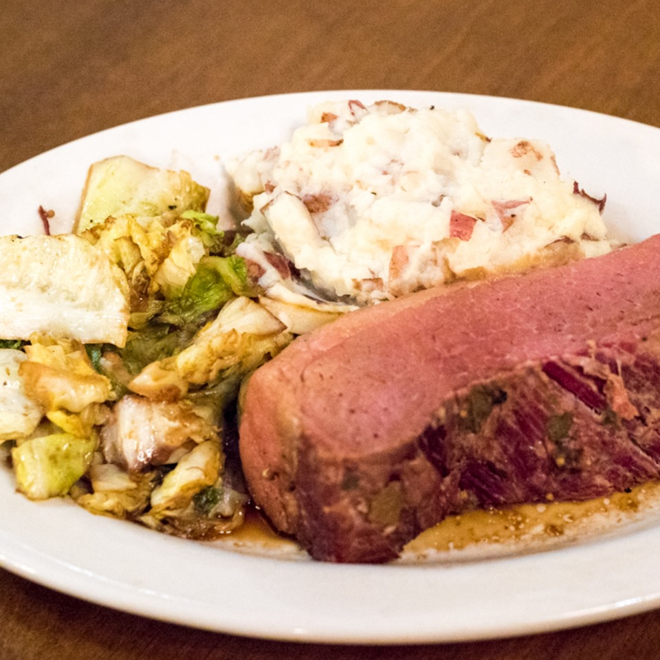 prime rib on a dish with roasted root vegetables and mashed potatoes