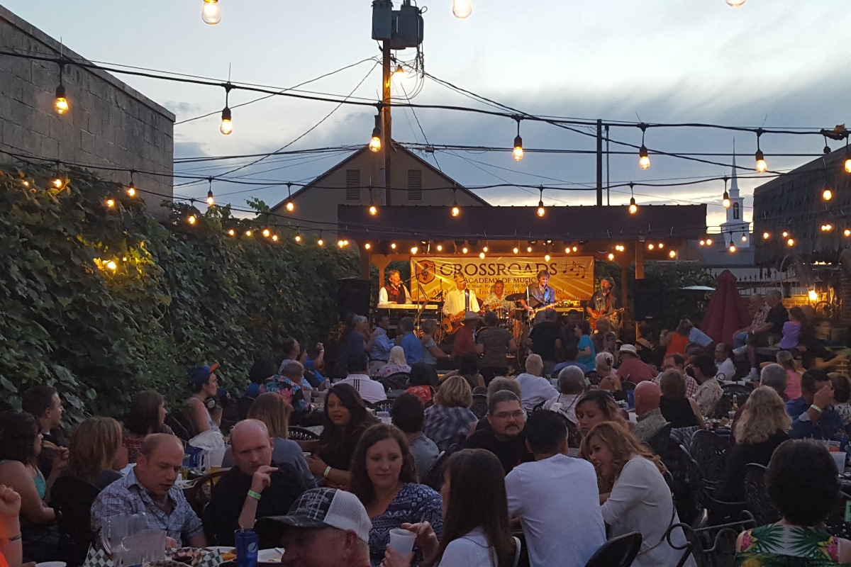 outdoor patio filled with people while a live band plays and string lights lit up overhead