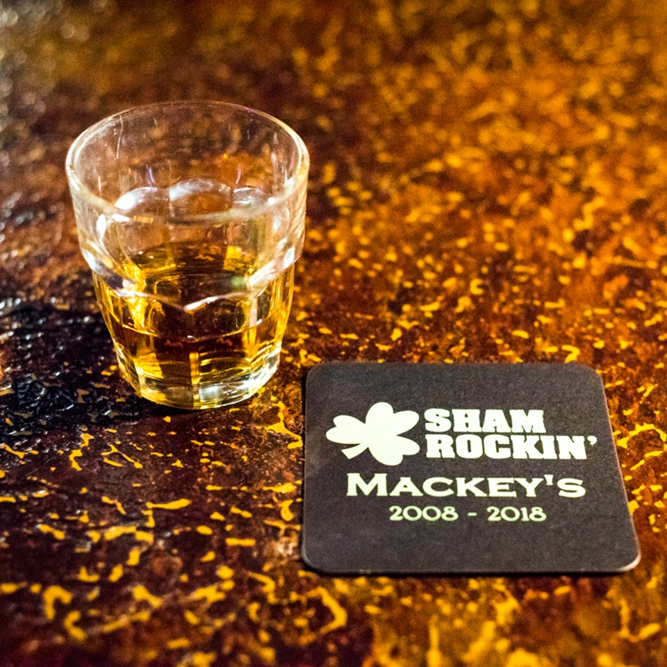 "glass of whiskey on the bar with a coaster that says ""Sham Rockin, Mackey's 2008-2018"""