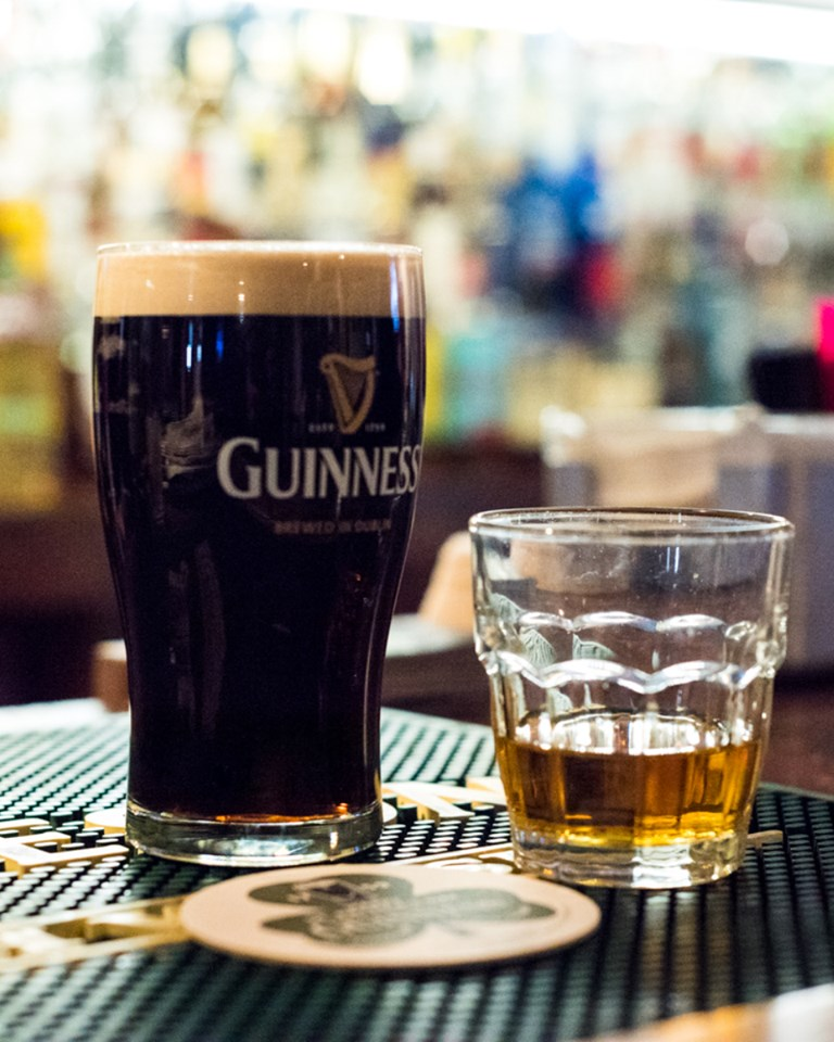 glass of guinness and glass of whiskey on bar
