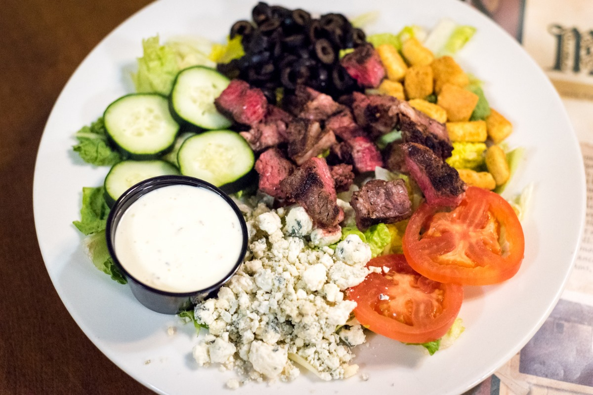 salad with romaine, tomatoes, croutons, cucumbers, grilled steak slices, black olives, blue cheese crumbles and a side of blue cheese dressing
