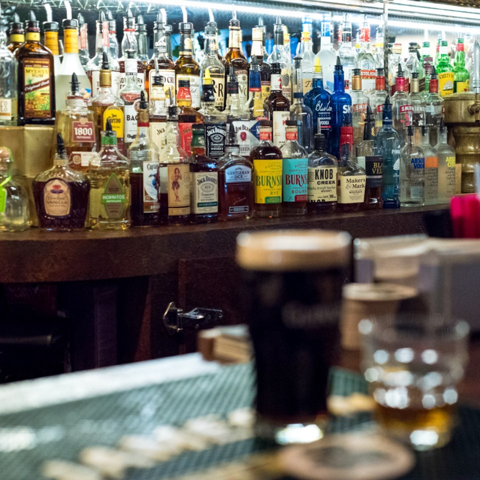 various liquor bottles on the bar with a glass of guinness beer on the bar top