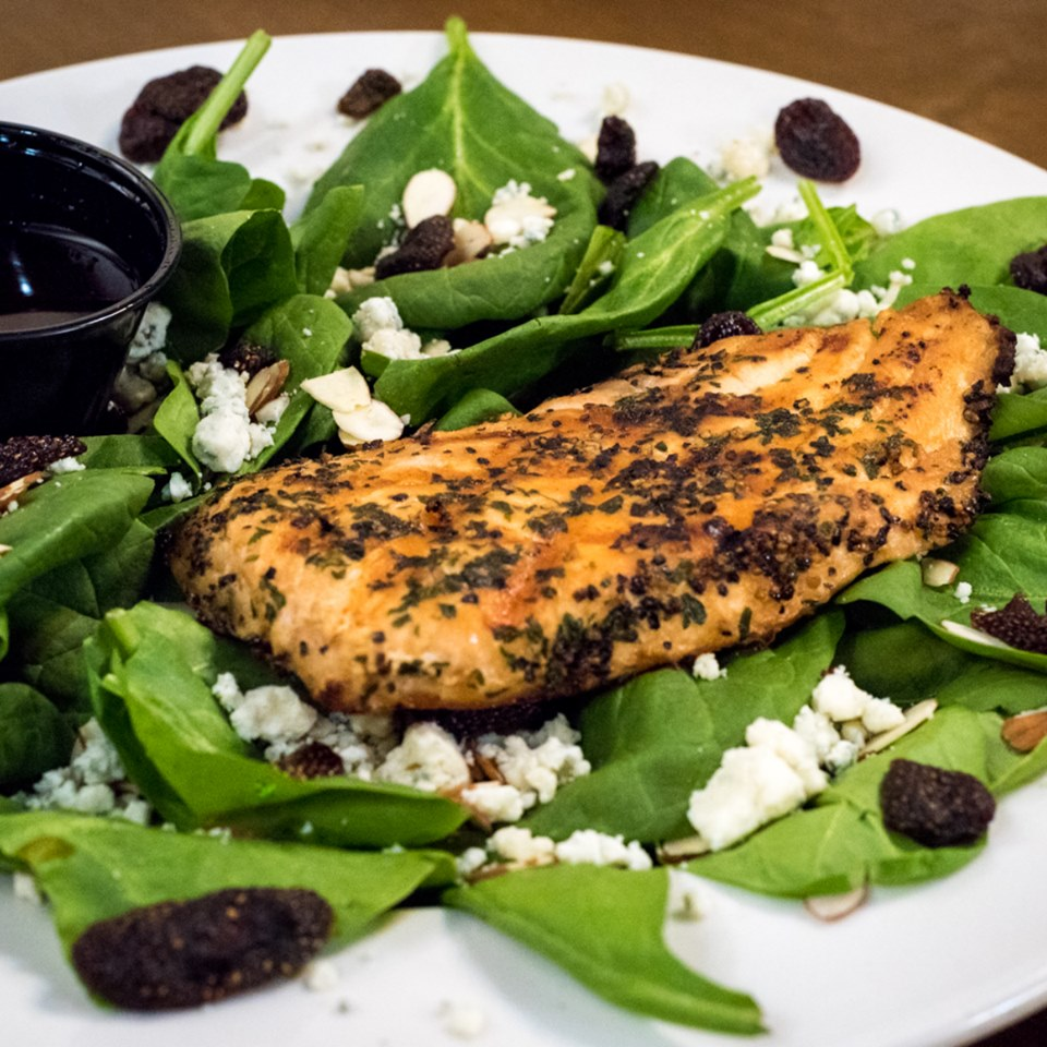 grilled chicken on top of a salad with spinach leaves, craisins, goat cheese and a vinaigrette