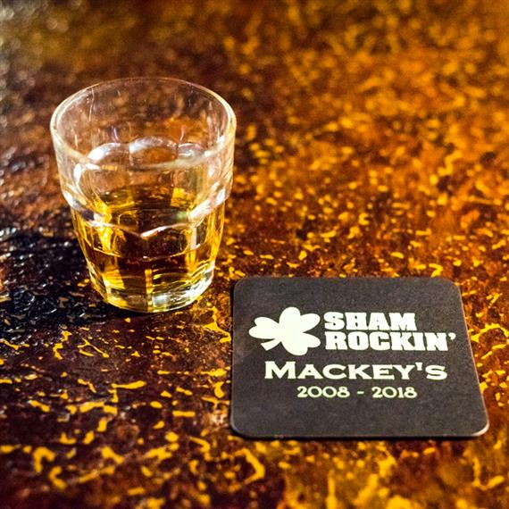 "glass of whiskey on the bar with a coaster that says ""Sham Rockin' Mackey's 2008-2018"""