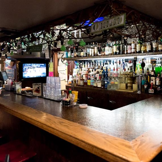 bar with various alcohol bottles and irish clad decorations