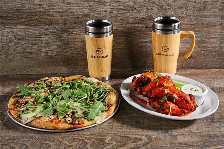 a plate of pizza and a plate of wings with seaside bar mugs