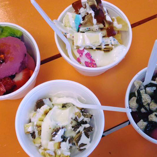 4 cups of frozen yogurt with assorted candy toppings