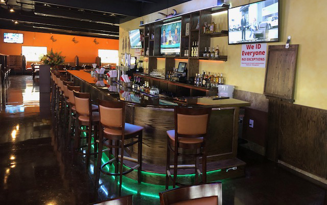 Wooden bar with empty bar stools surrounding it