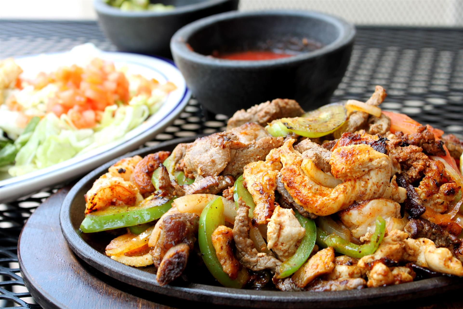 Chicken fajita on a skillet with peppers and onions and a small bowl of salsa
