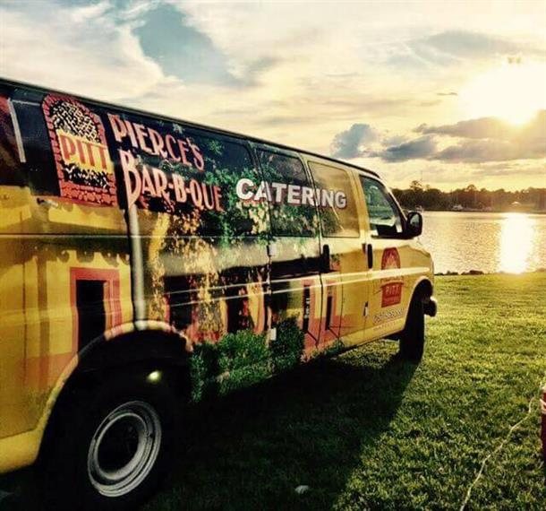 pierce's pit catering van in front of a lake during the sunset