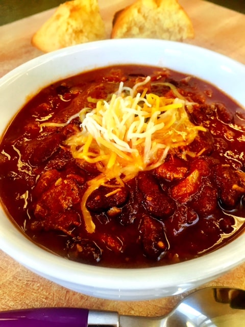 chili topped with shredded cheese and served with ornbread