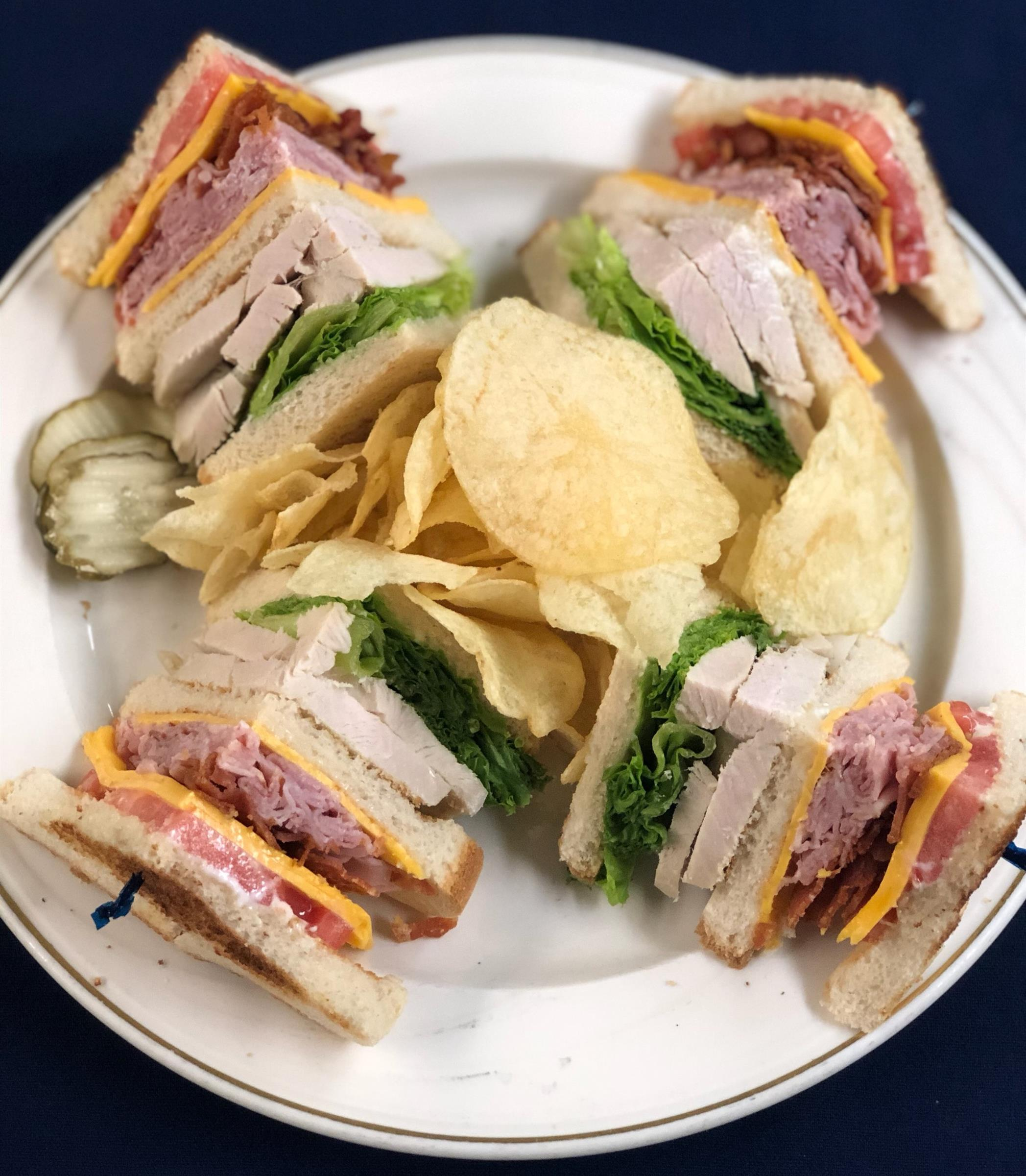 Turkey club sandwich with lettuce, cheese, ham, bacon and cheddar cheese with potato chips