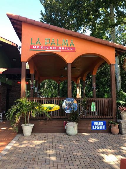 exterior of the restaurant with plants and sign on the building that says La Palma Mexican Grill