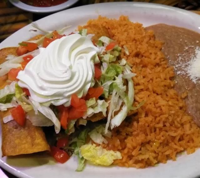 tacos topped with sour cream, lettuce, and tomato served with rice and refried beans