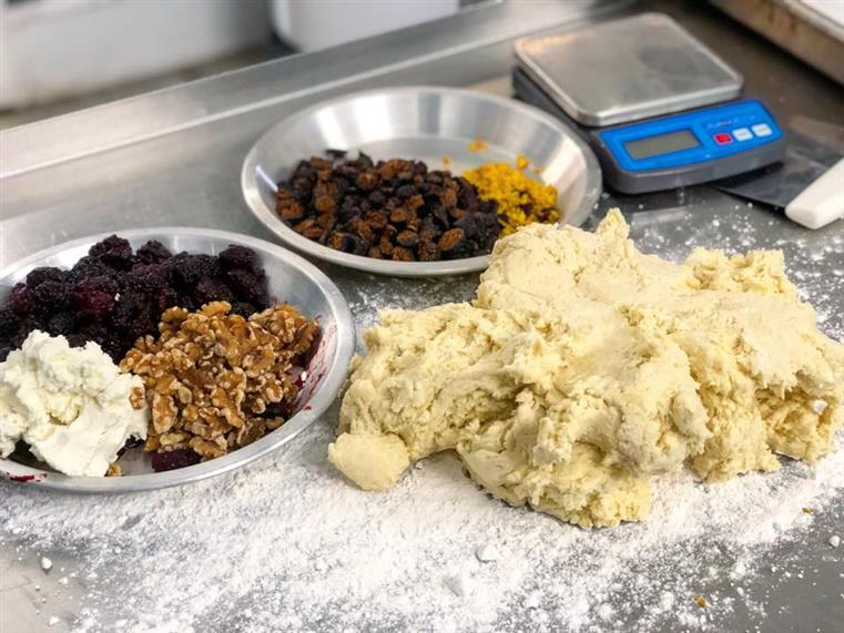 pie baking mix with dough, raisins, blackberries, nuts, and a scale