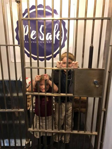 jail cell with two children behind bars