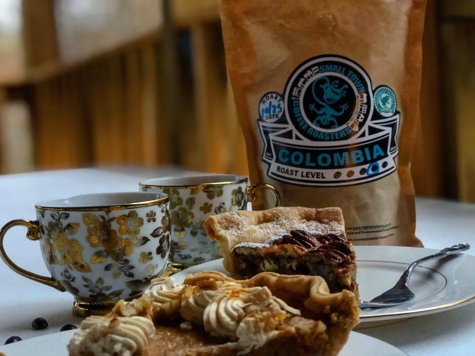 two pastires platted with two vintage mugs and a bag of columbia coffee