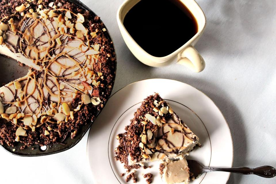 peanut butter pie with a slice cut out on a plate with a cup of coffee