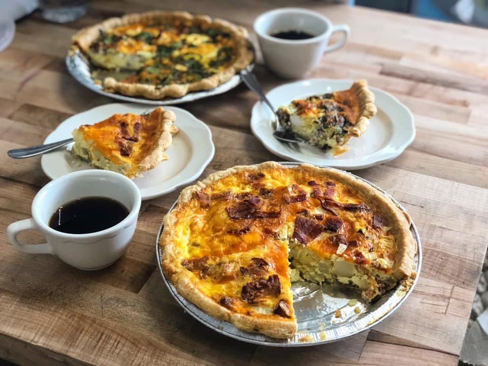 two quiche's with two slices on plates with two cups of coffee
