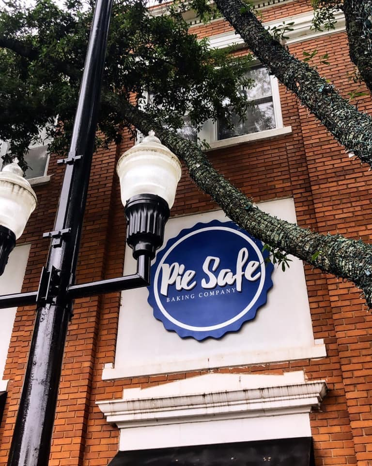 exterior Pie Safe Backing Company with sign, tree branch, and street light