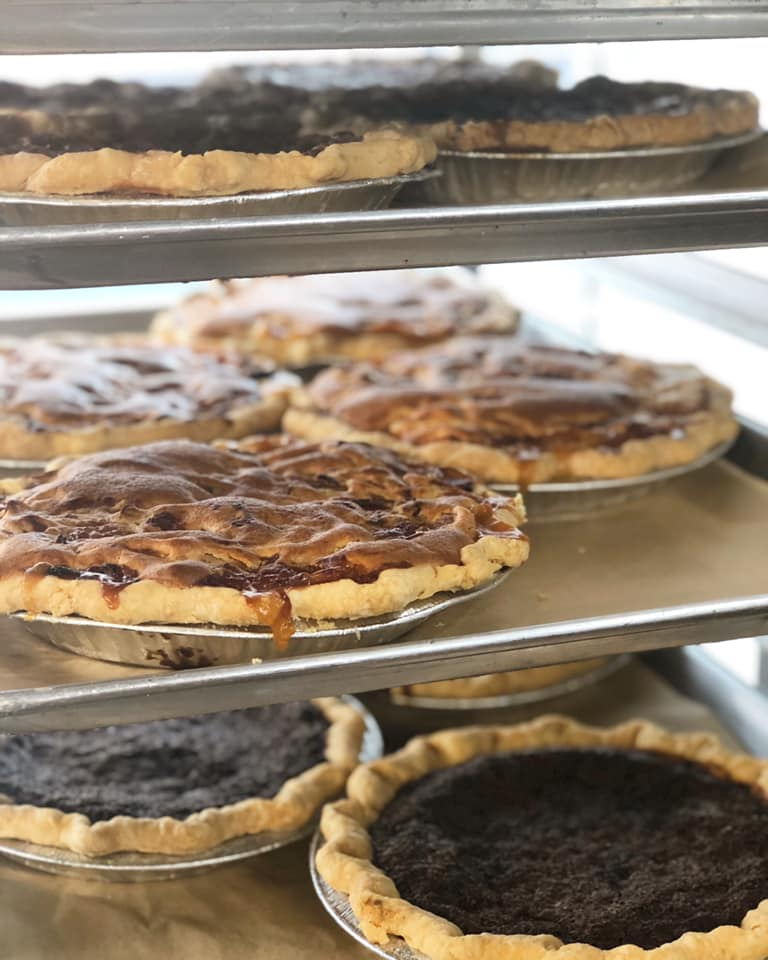 assortment of pies sitting on a rack
