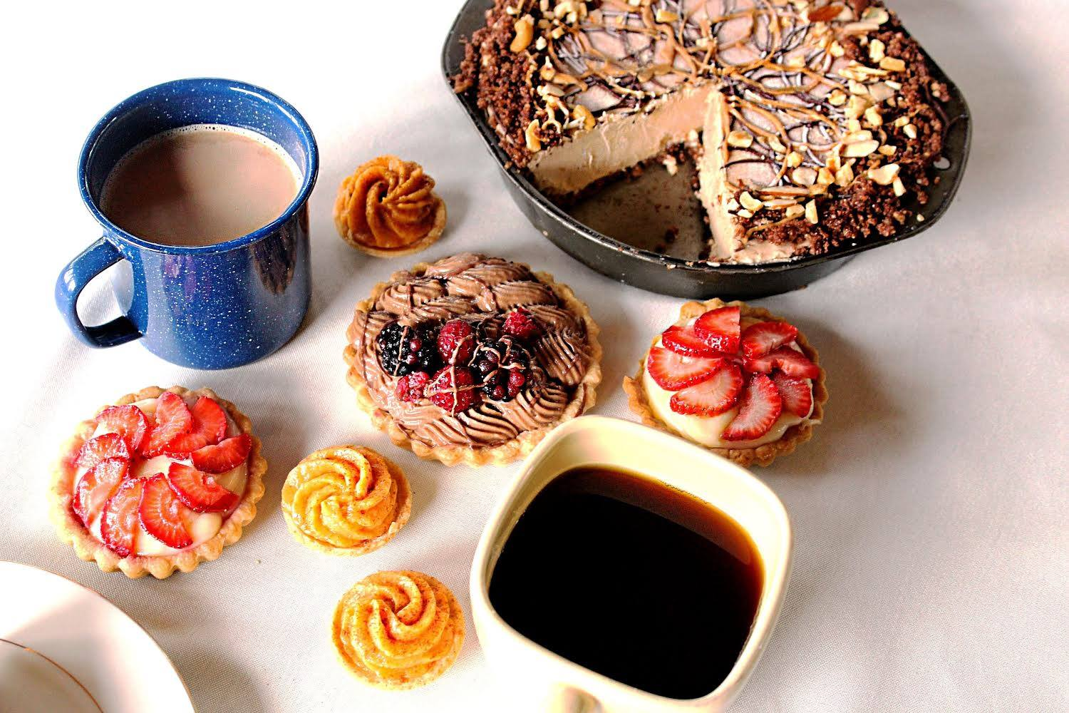 assortment of pastries and peanut butter pie with two mugs filled with coffee