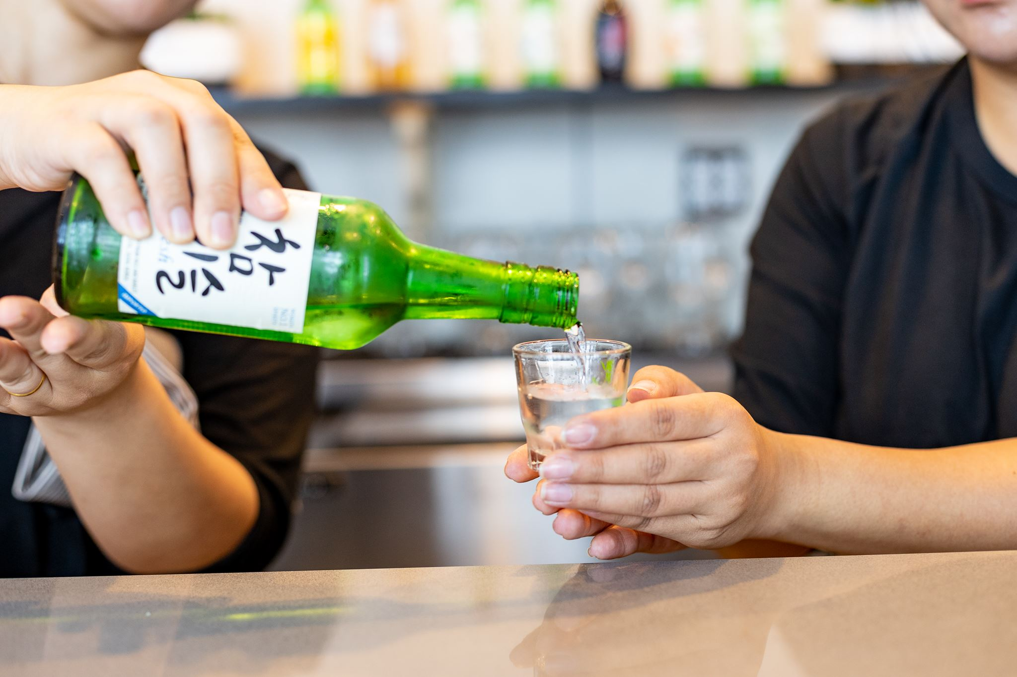 Man pouring Korean liquor into a shot glass