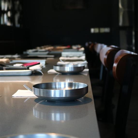 Empty table with empty metal bowls lined evenly along table