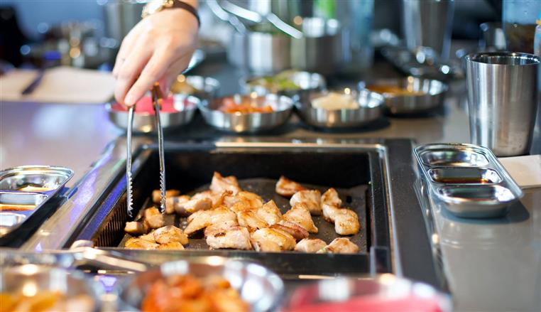 Person cooking diced chicken in metal pan with tongs