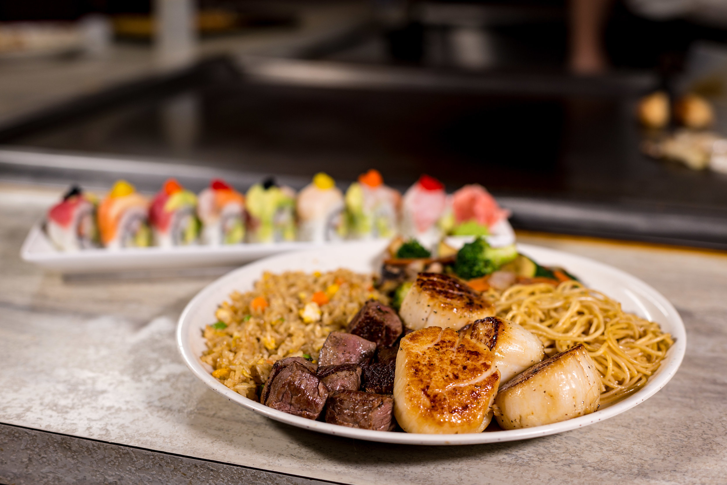 Seared scallops and diced steak dish with fried rice and a sushi plate