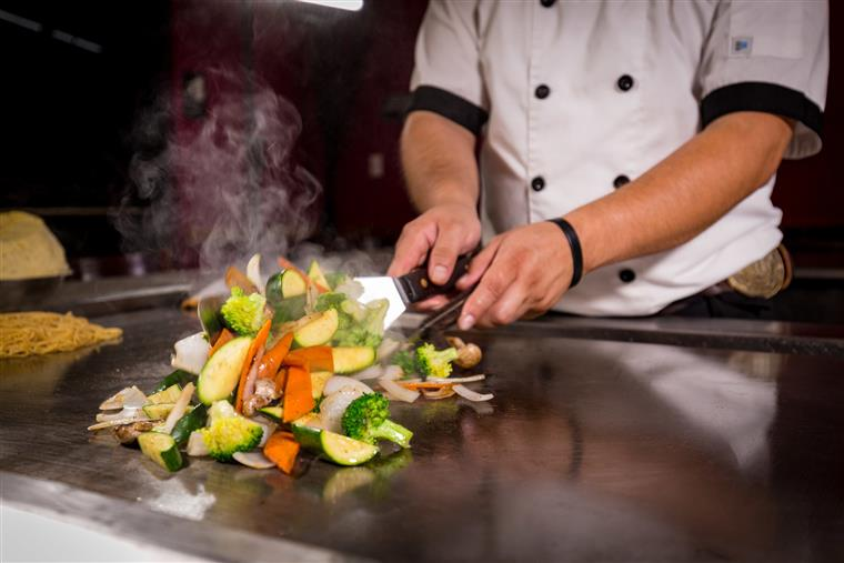 Chef tossing cut vegetables on hibachi grill