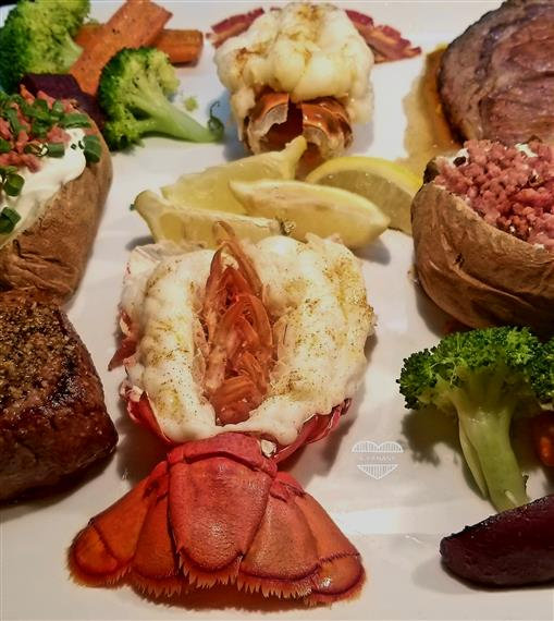 Surf and Turf with a side of baked potatoes and cooked vegetables