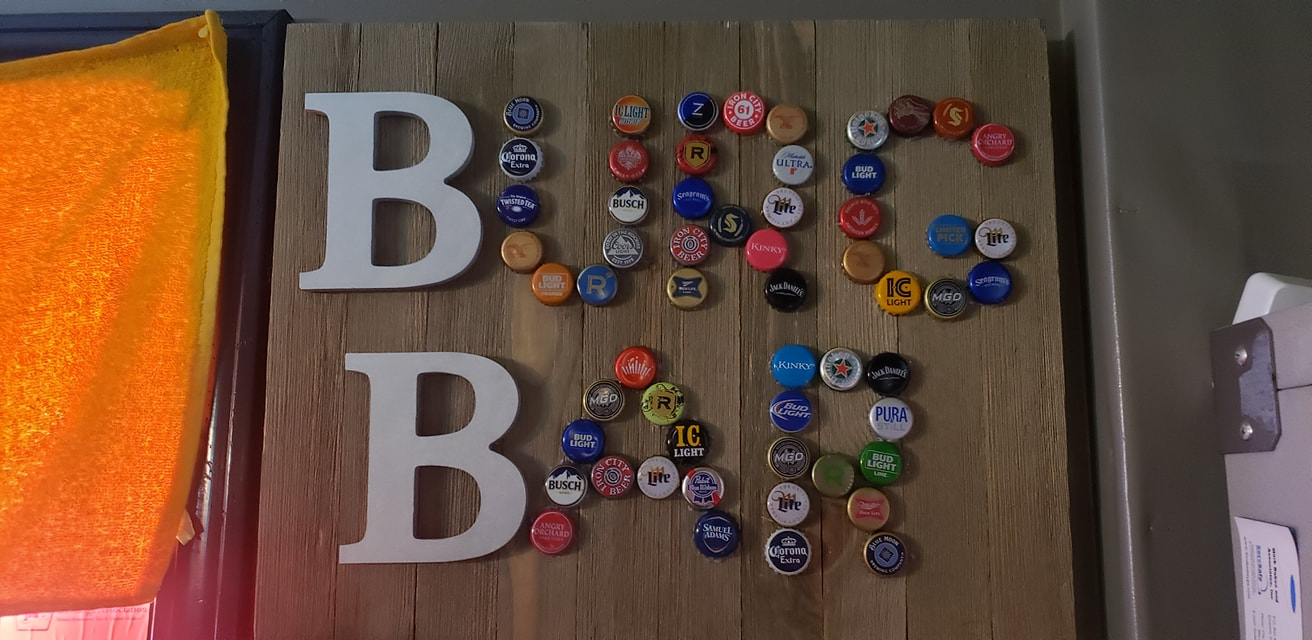 Bottle caps on wooden table spelling out Burg Bar