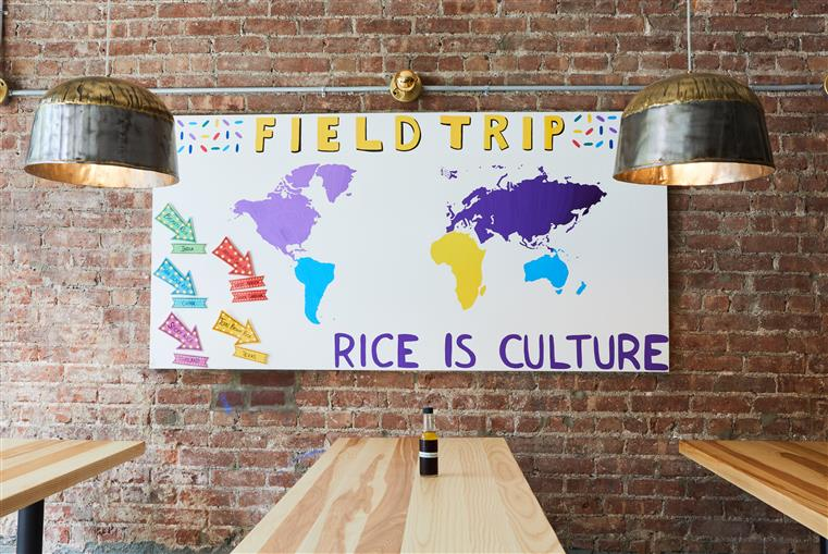 "Three wood high-top tables against the brick wall witha painting of a colorful map and says ""Fieldtrip. Rice is Culture."""