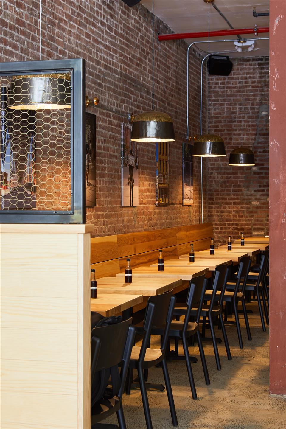 row of wood tables against a brick wall