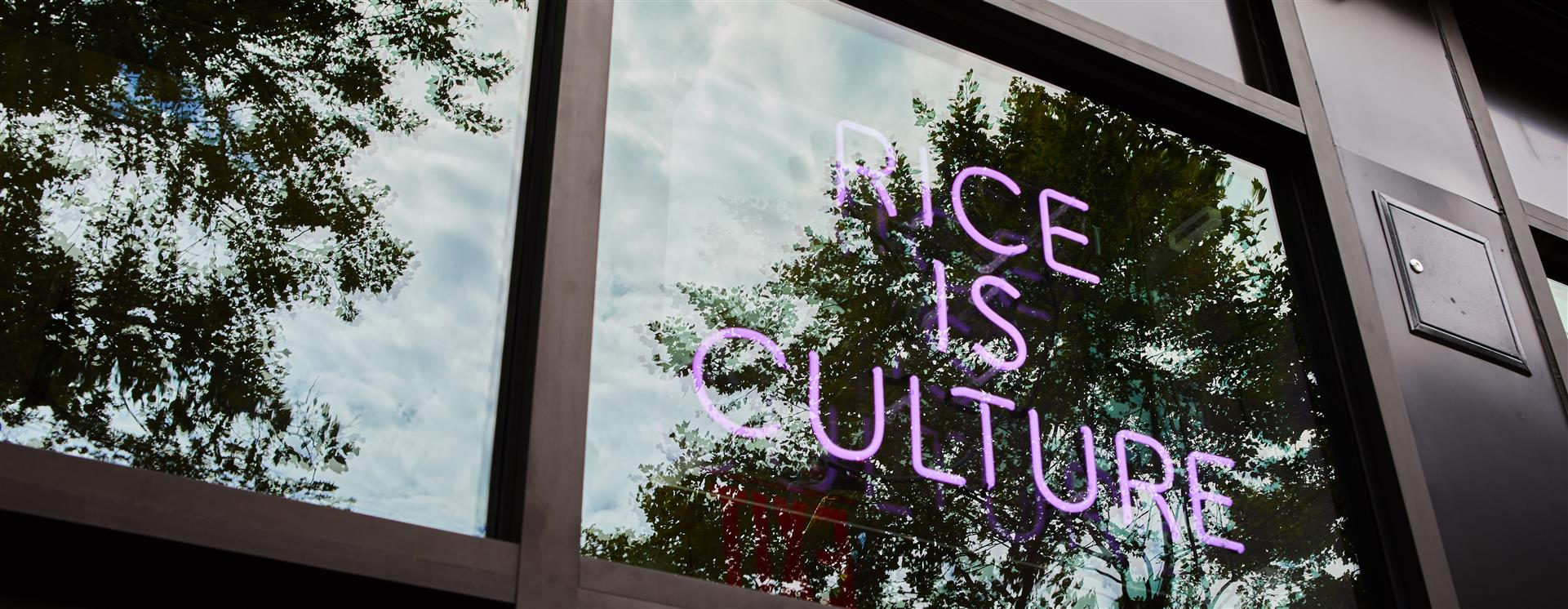 "Neon sign in the window at Fieldtrip that says ""rice is culture"""