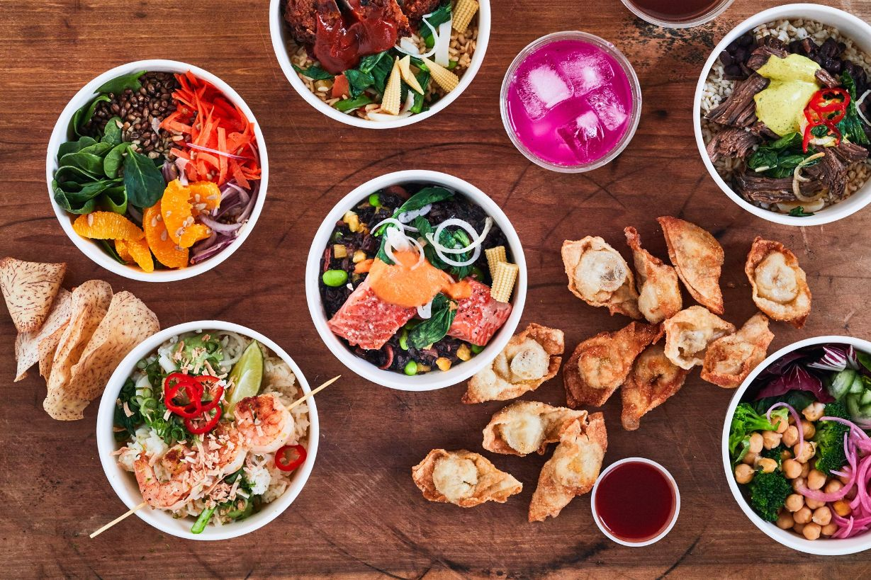 Assorted rice bowls including Salmon, braised beef, crispy chicken, shrimp and veggie bowls, a baby spinach grain salad, yucca puffs, crab pockets and a cup of dragonfruit lemonade on a wood table.
