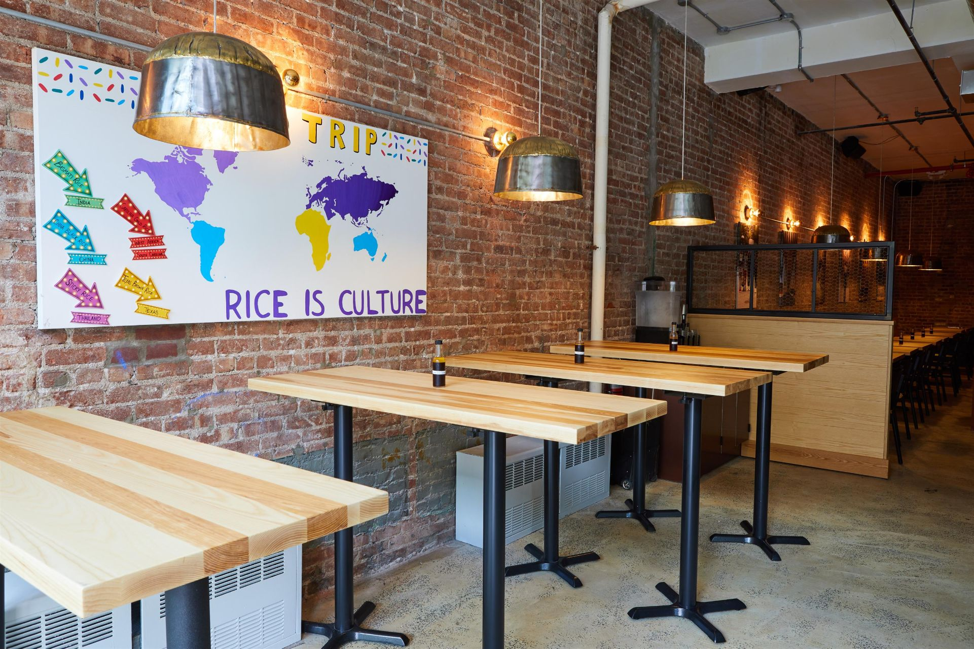 """four high-top wood tables against a brick wall with a painting that says """"Fieldtrip. Rice is Culture."""""""