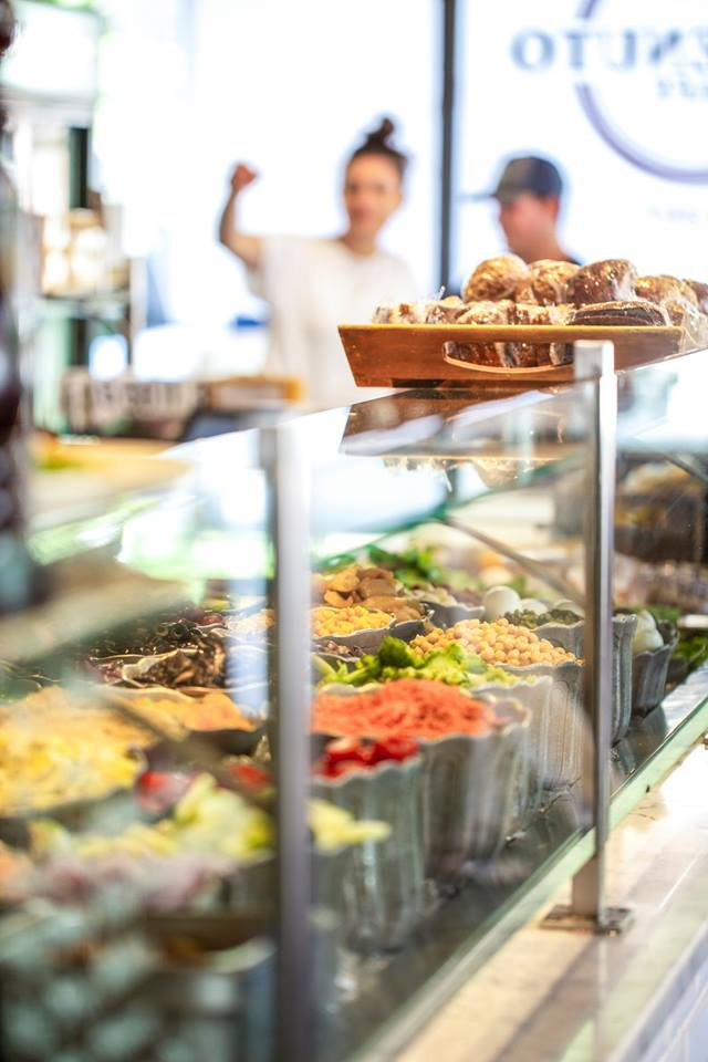 Salad bar behind a glass window with pastries on top