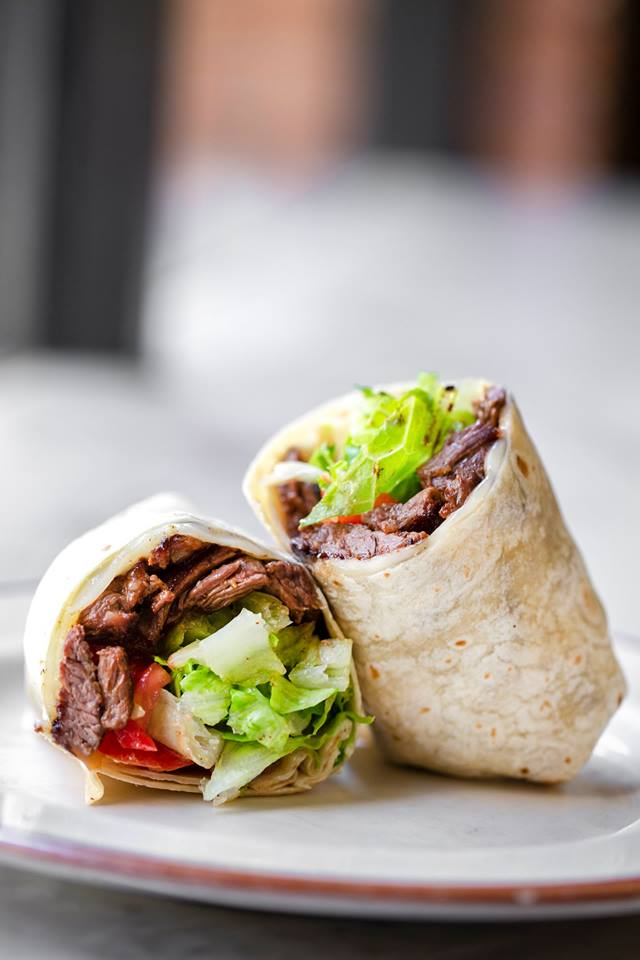 Steak wrap on plate with lettuce and tomates
