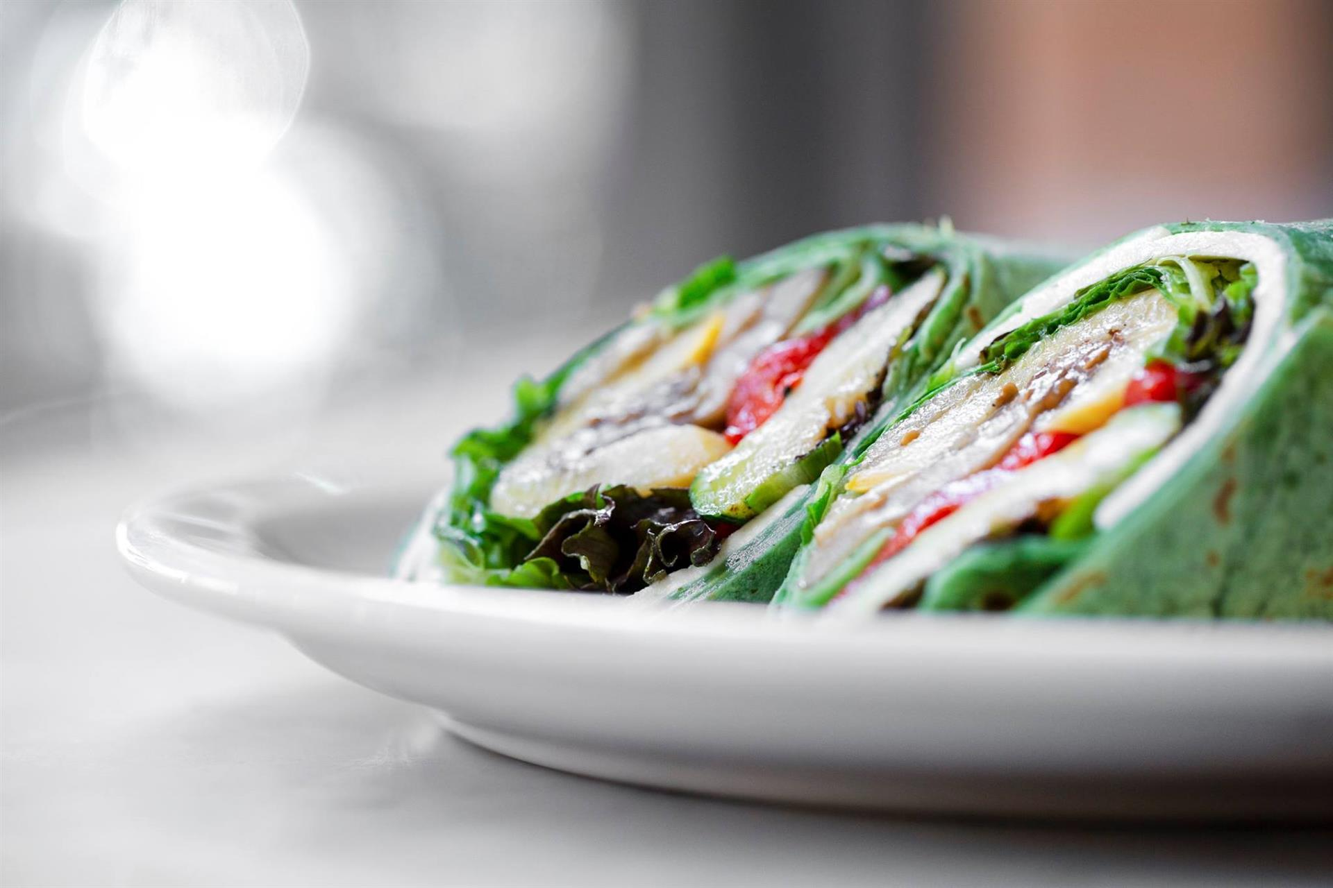 Spinach wrap stuffed with veggies, peppers, and lettuce