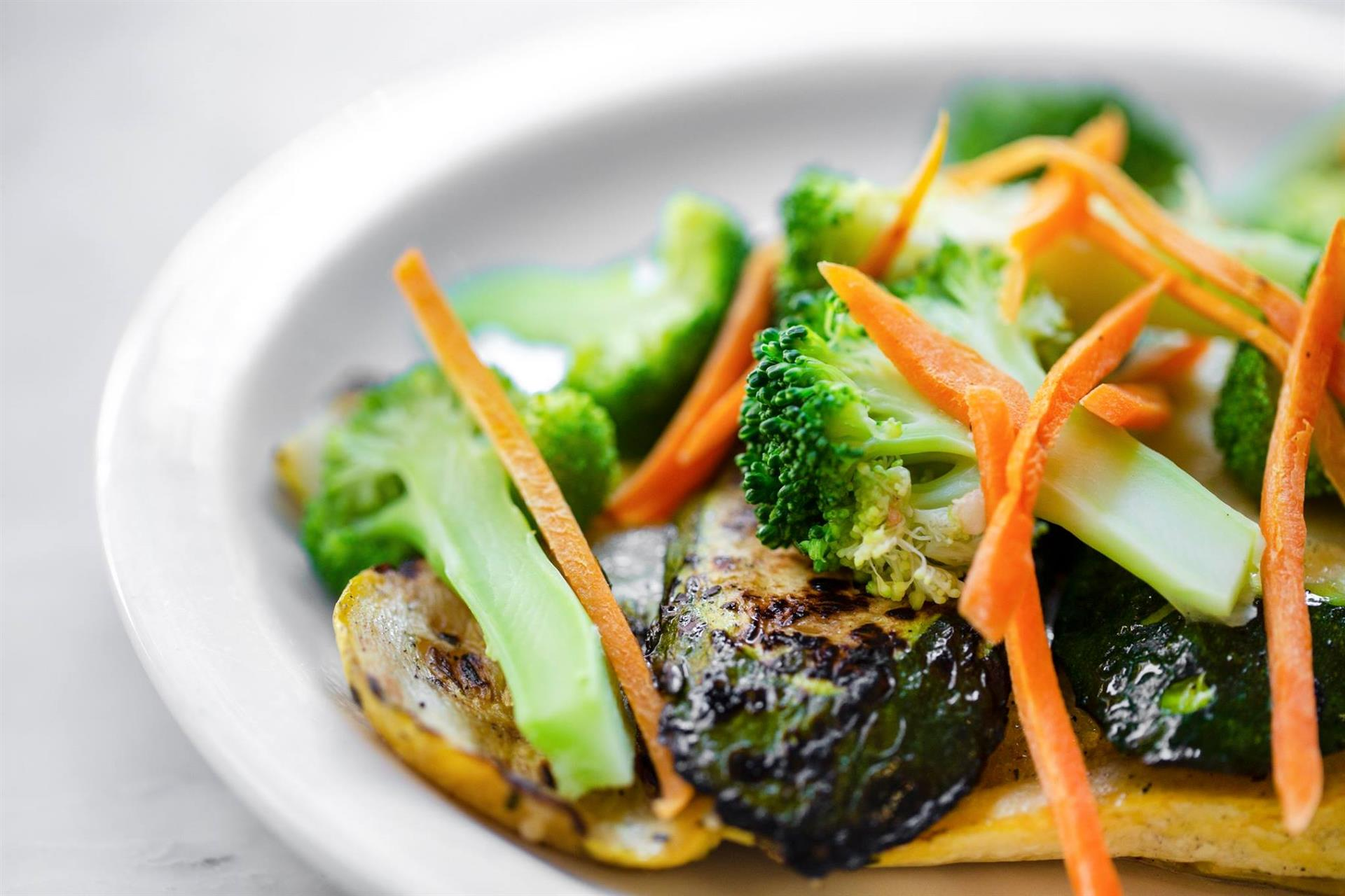 Plate of broccoli, brussel sprouts, and sliced carrots