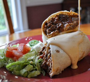 Beef burrito smothered in melted cheese and lettuce on plate